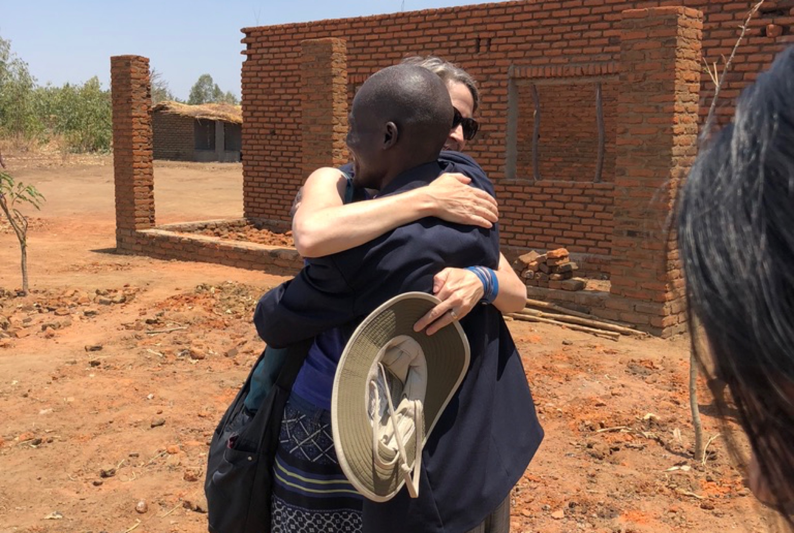 A woman and a man are hugging each other.