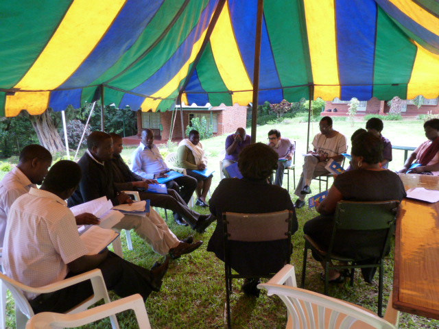 A group of people is sitting in chairs under a tent.