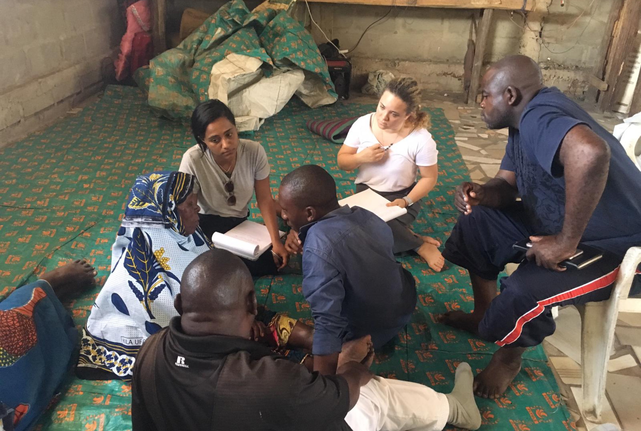 Three women and two men are sitting on the ground, and a man is sitting in a chair. Everyone is listening to a woman wearing a blue headscarf and sitting on the ground.