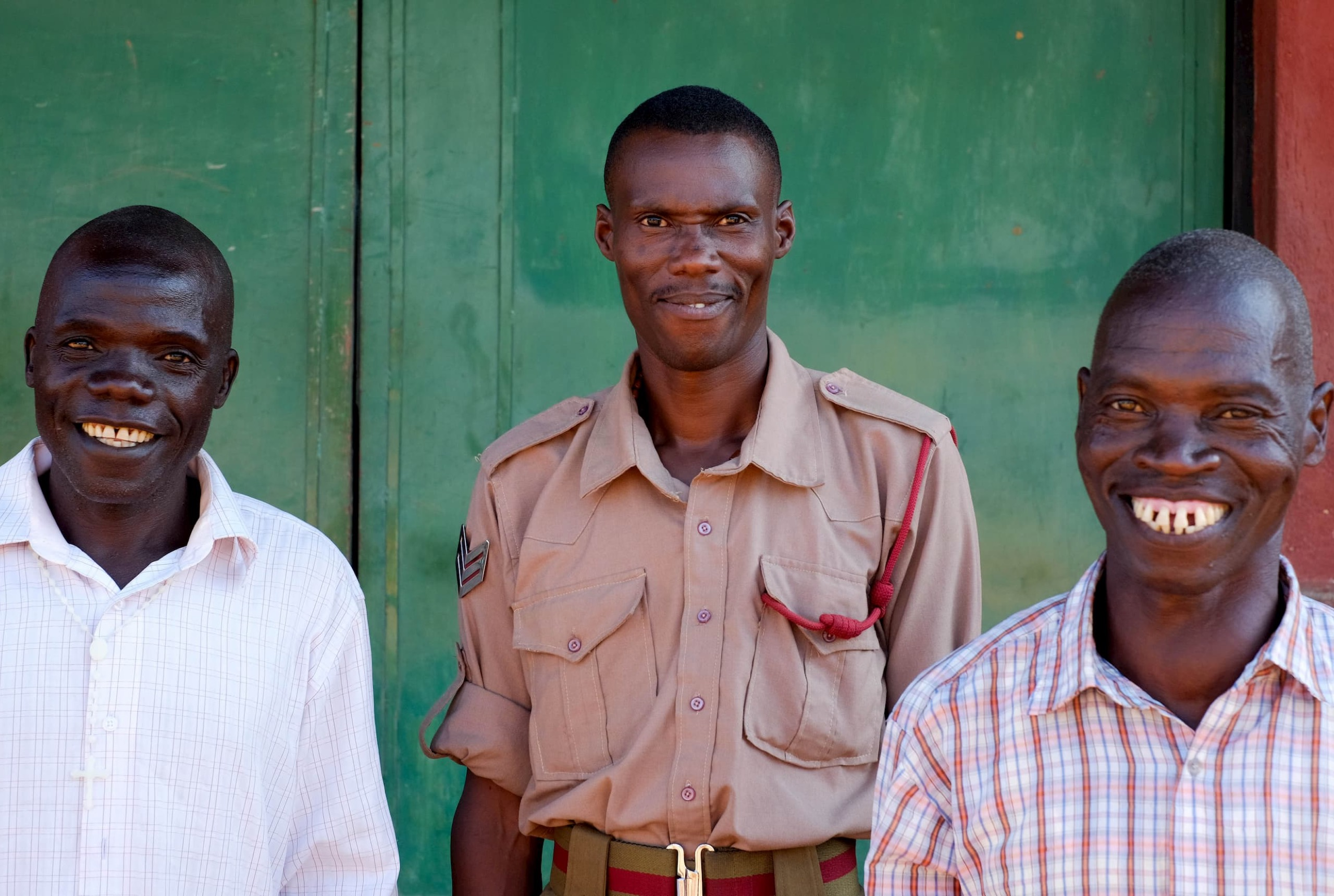 A man in a white shirt, a man in a beige uniform, and a man in a plaid shirt are looking at the camera and smiling in front of a green building.