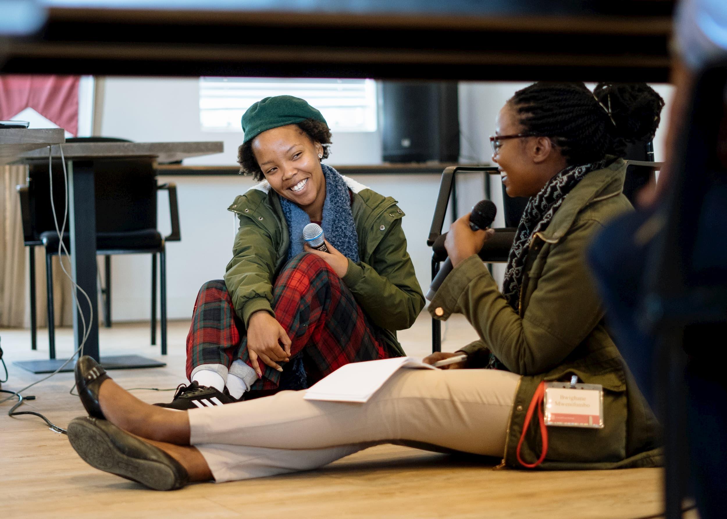 Deux femmes en vestes vertes sont assises par terre et se parlent dans des microphones.