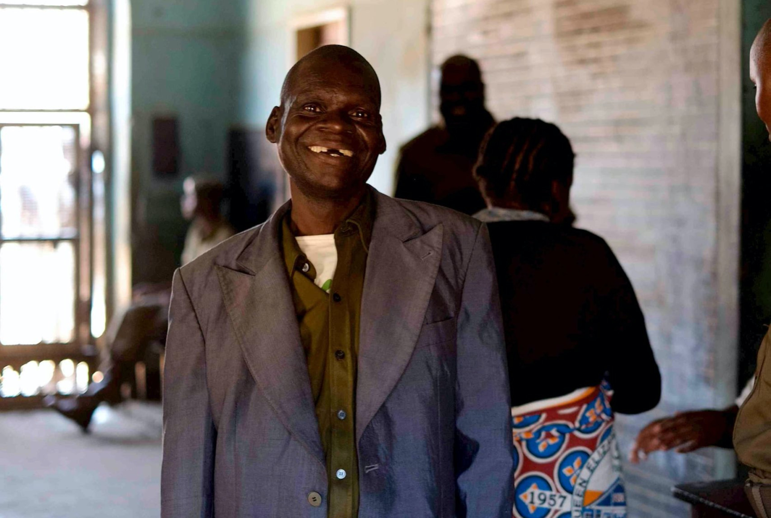 A man in standing and smiling at the camera.
