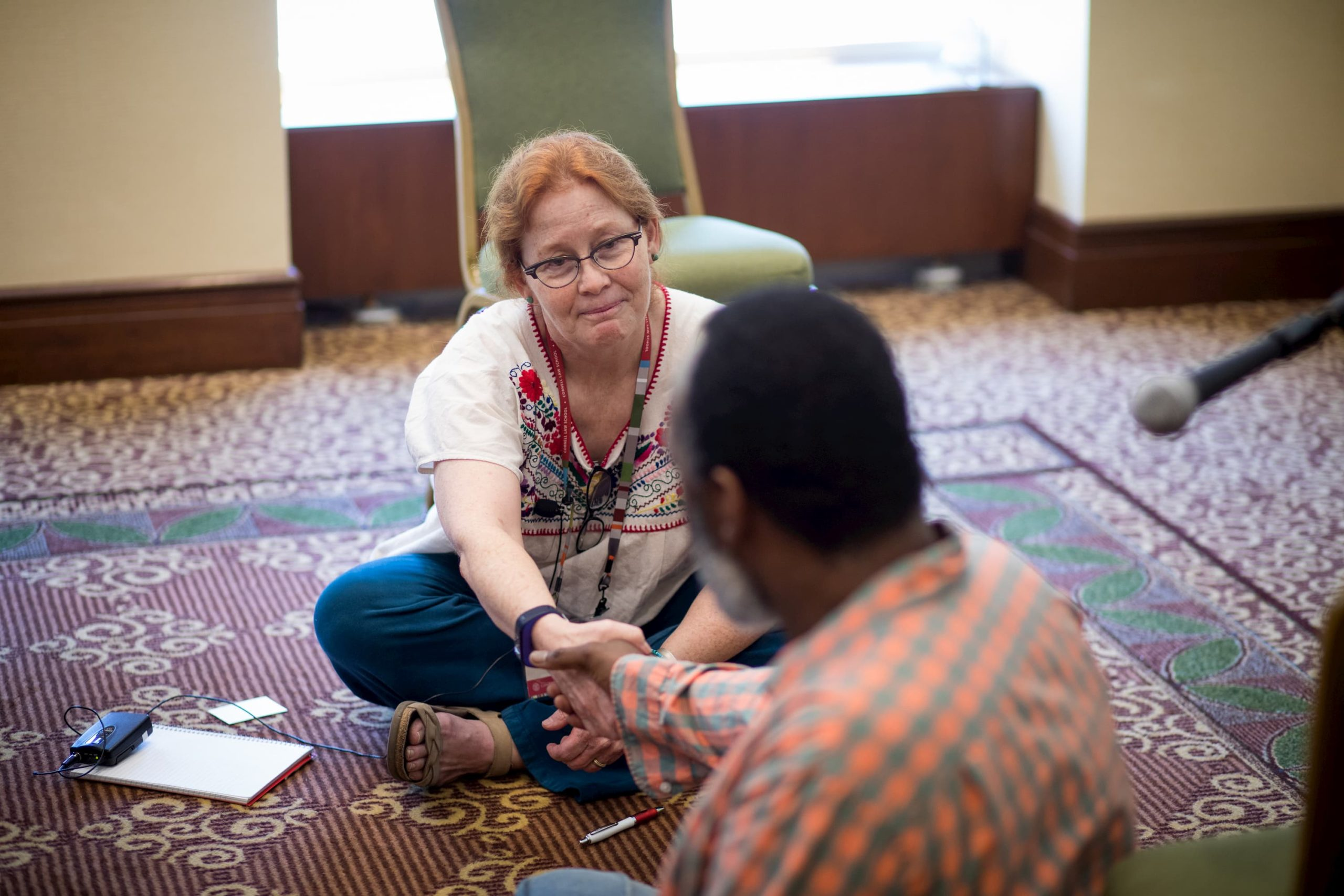 A woman with glasses and in a white shirt with embroidery is sitting on the ground, holding hands with a man in an orange plaid shirt.