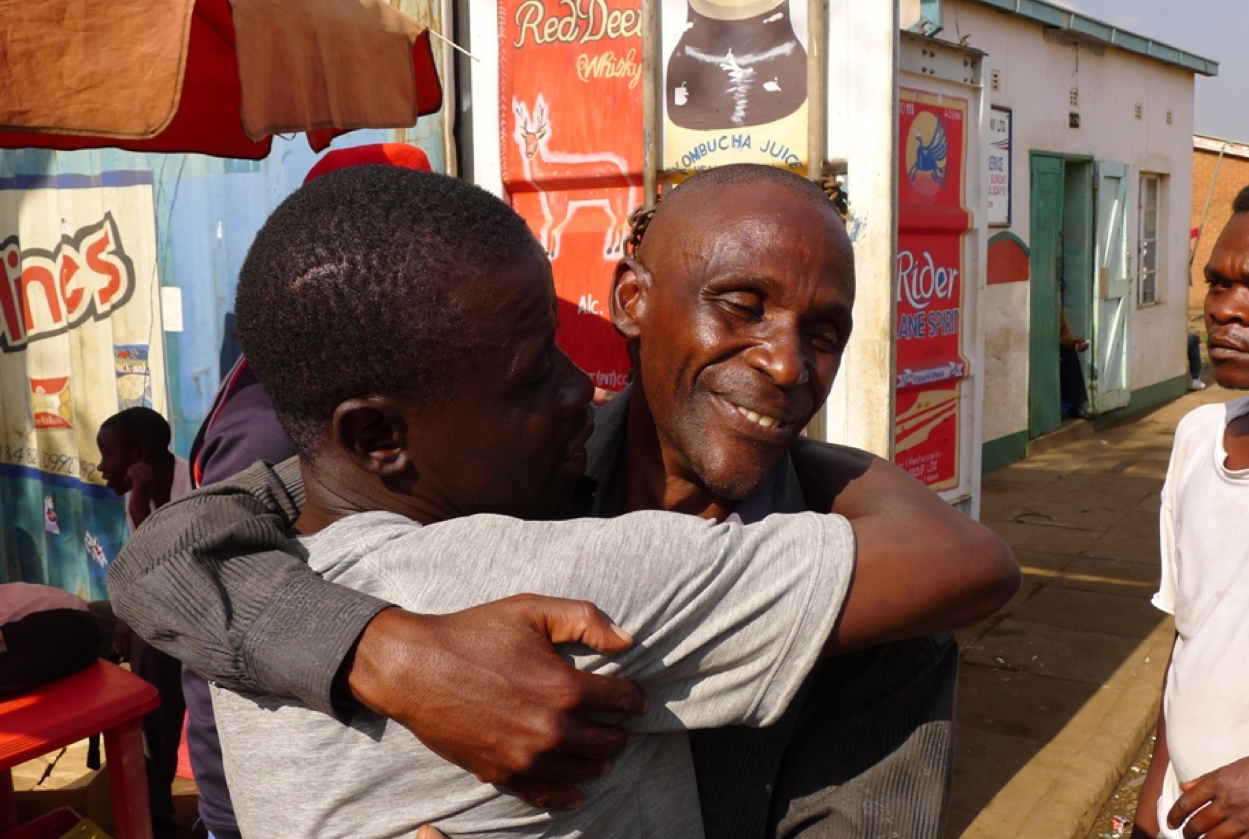 A man in a gray shirt and a man in a black shirt hugging each other.