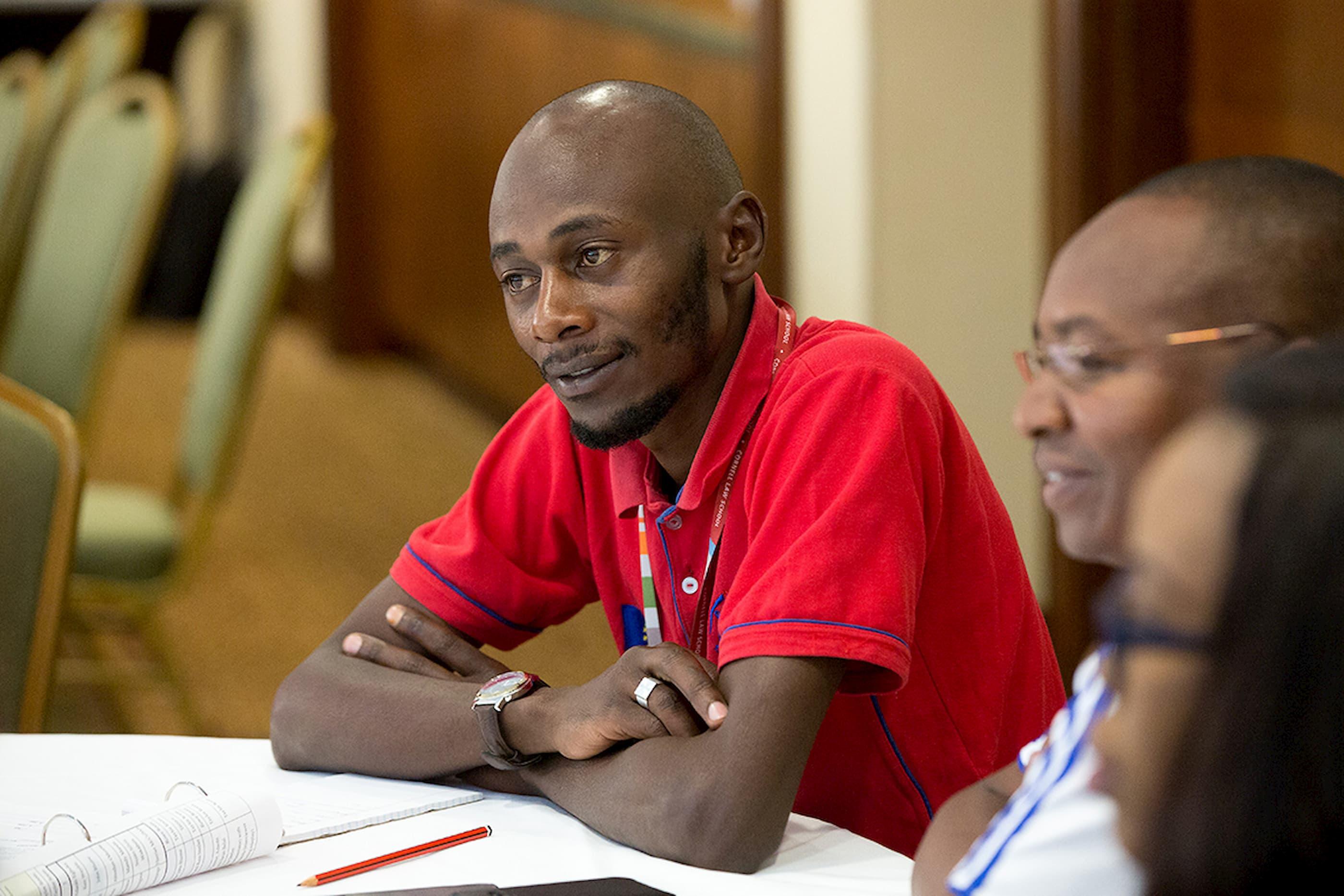Un homme en chemise rouge est assis à une table et regarde à la gauche.