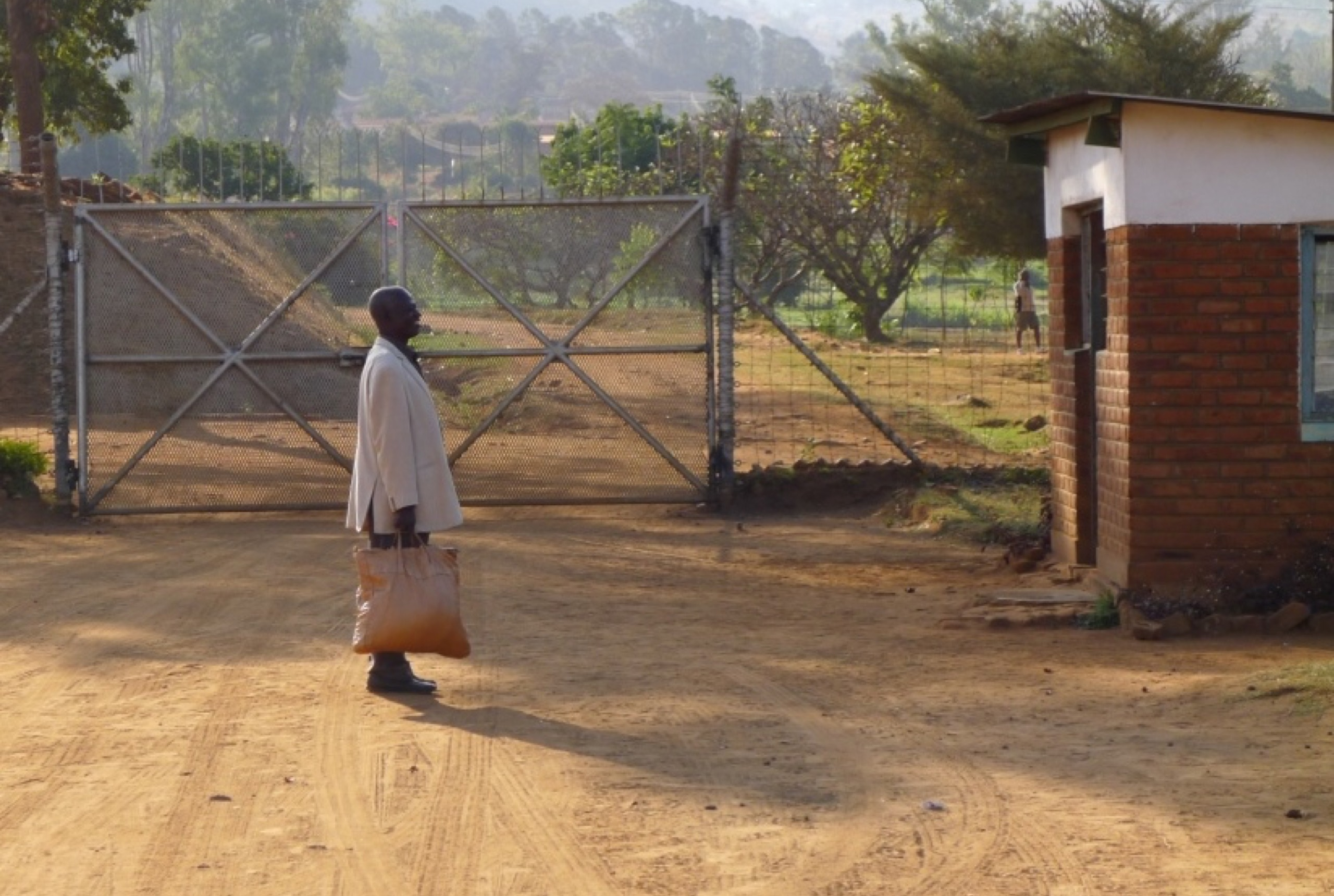 A man in a light-colored jacket is standing in front of a wire gate, holding a bag and standing sideways to the camera.