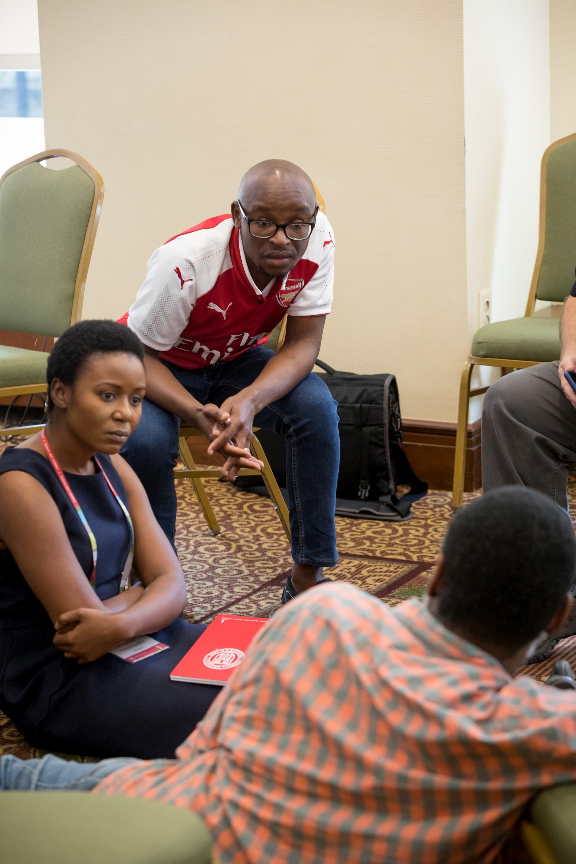 Une femme en robe noire est assise par terre à côté d'un homme en chemise rouge qui est assis sur une chaise. Les deux regardent un homme en chemise orange à carreaux qui est assis par terre devant eux.
