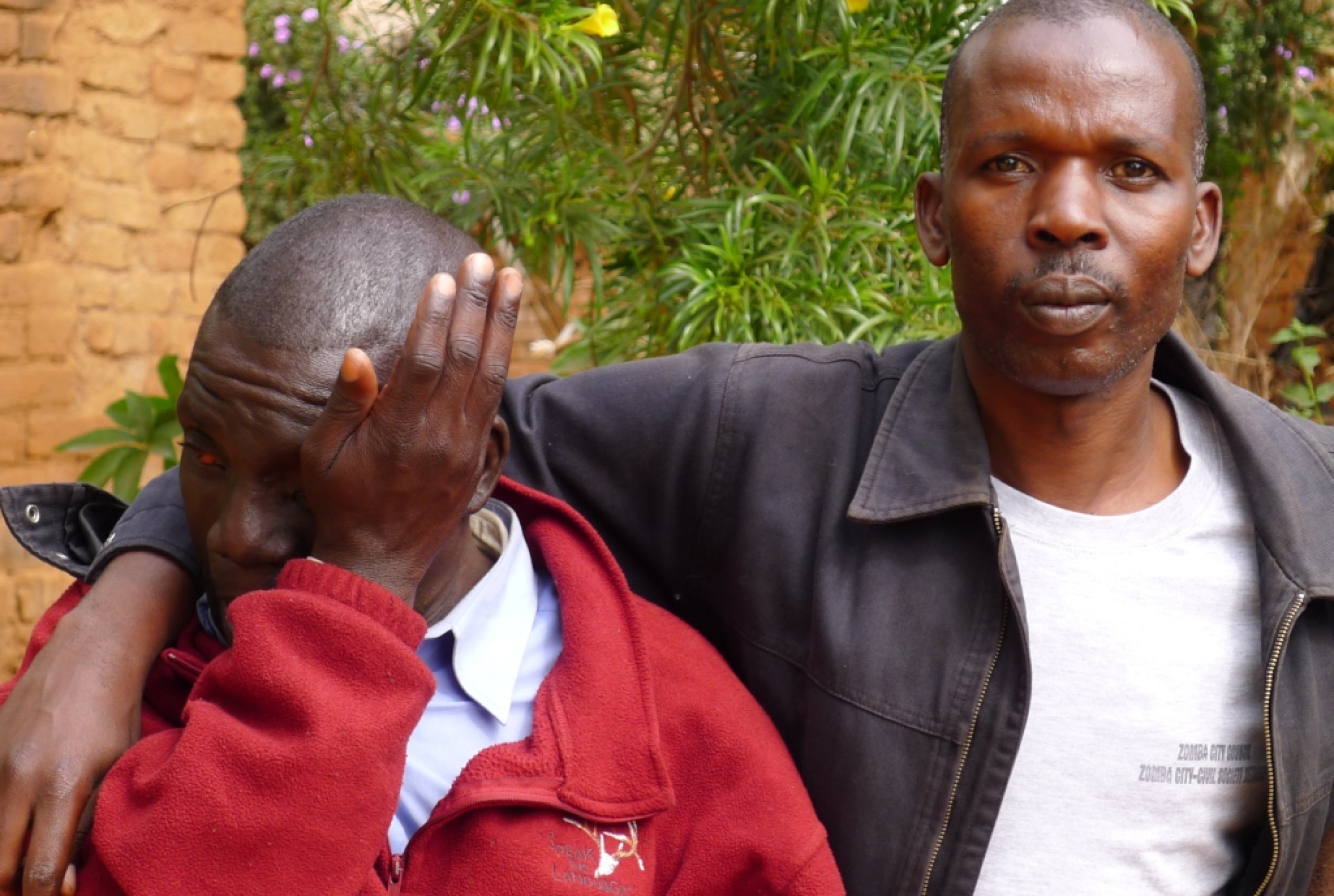 A man in a black jacket has his arm around a man in a red jacket, who is wiping tears with his hand.