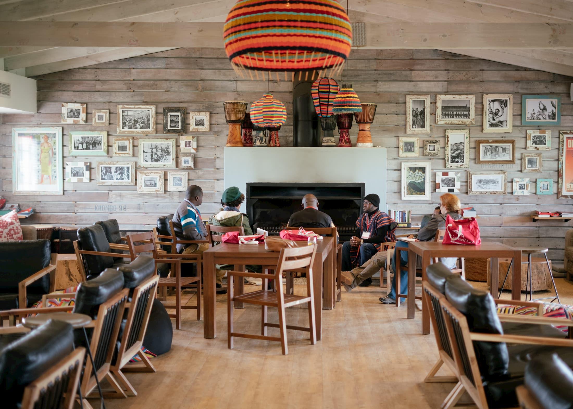 Six personnes sont assises sur des chaises en demi-cercle autour d'un feu de cheminée. Il y a des tableaux sur le mur à côté du foyer et quelques tables et chaises vides dans la salle.