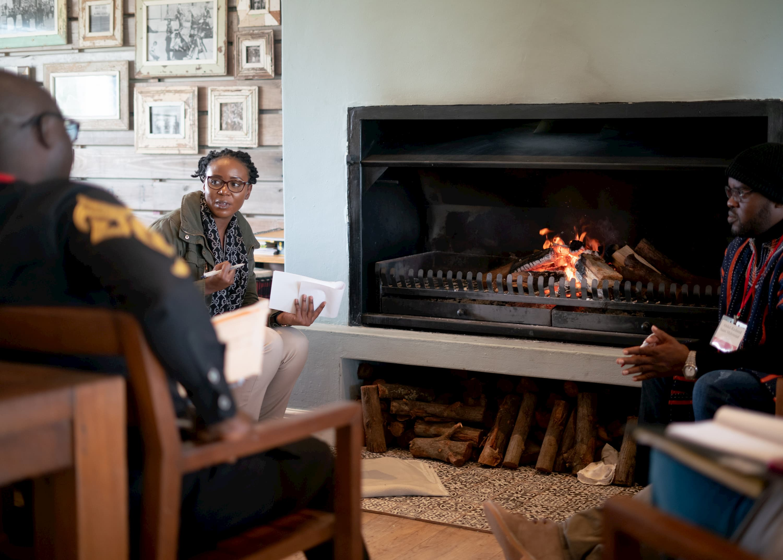 Une femme en veste verte et deux hommes en vestes noires sont assis autour d'un feu de cheminée. La femme tient un stylo et un carnet et regarde l'homme à côté d'elle, et l'autre homme regarde la femme.