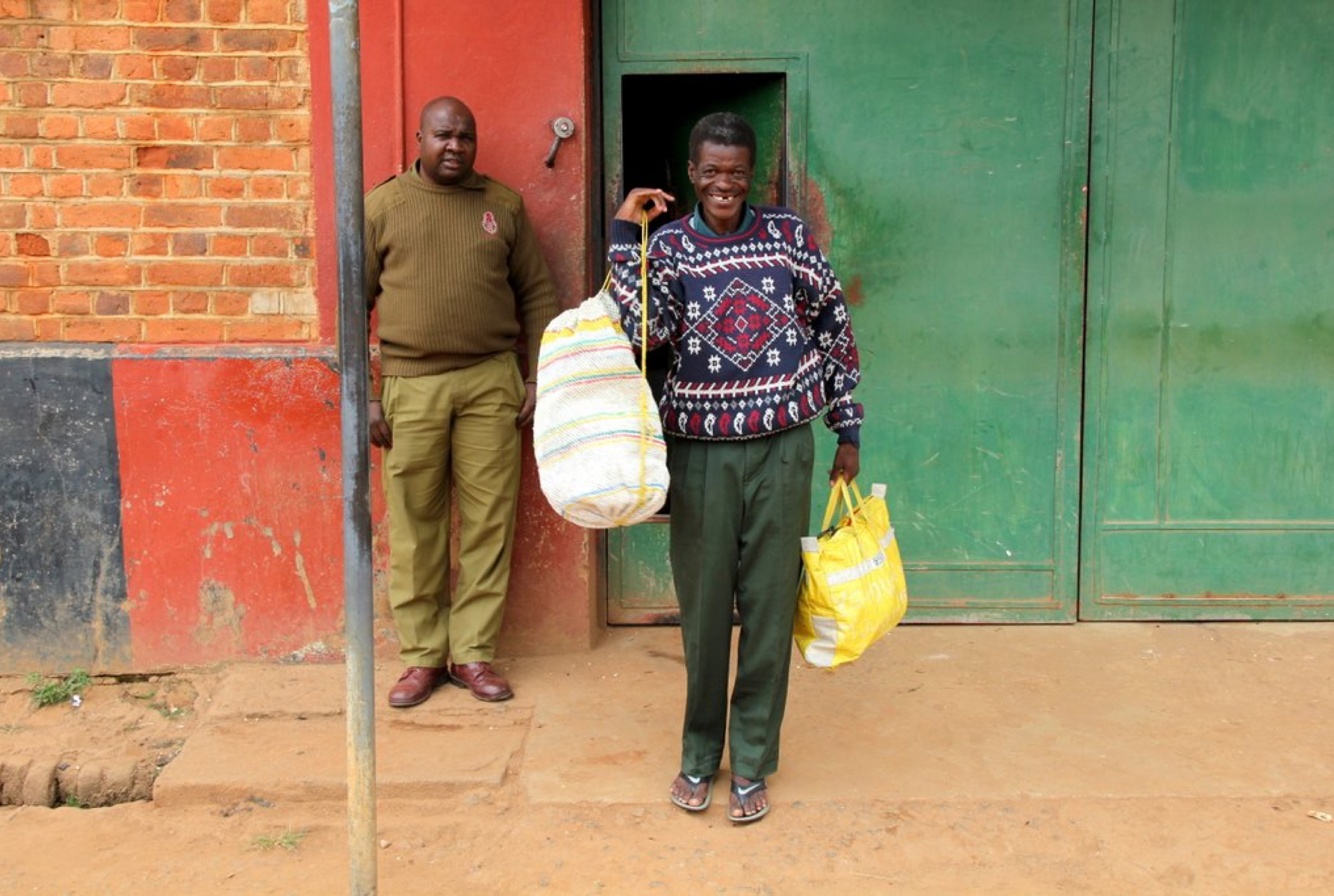 A man in a patterned sweater standing in front of a green and red building and holding two bags, smiling. A man in a brown shirt is standing in the back.