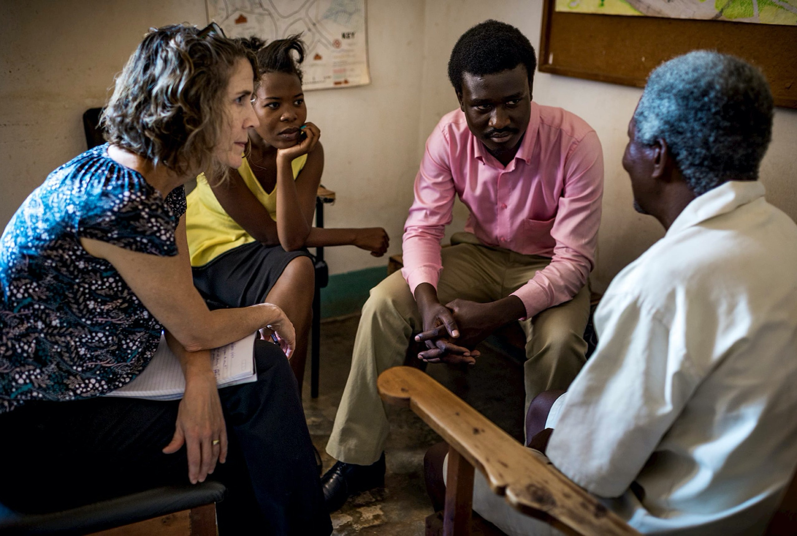 A woman in a blue patterned shirt, a woman in a yellow shirt, and a man in a pink shirt are looking at a man in a white shirt whose back is turned to the camera. All four of them are sitting in chairs.