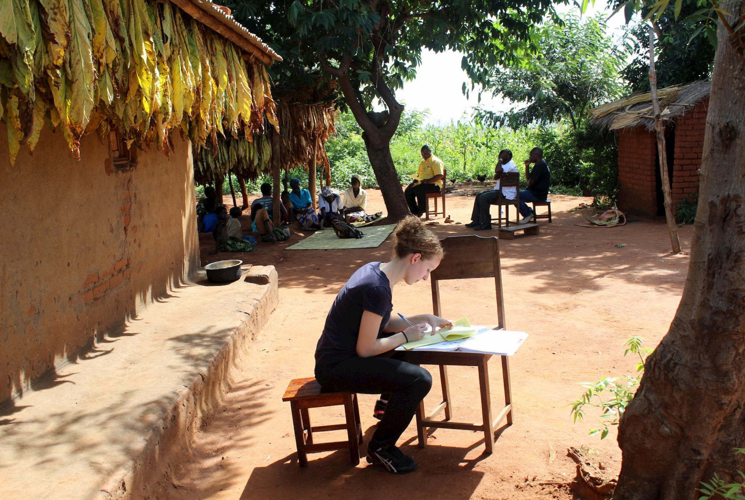 A woman in a dark-colored shirt is sitting on a stool and writing into a notepad outside. People are gathered around, some sitting on the ground and others sitting in chairs, further from the camera.