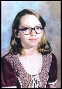 A young girl wearing glasses and a purple blouse poses for a picture, smiling slightly.