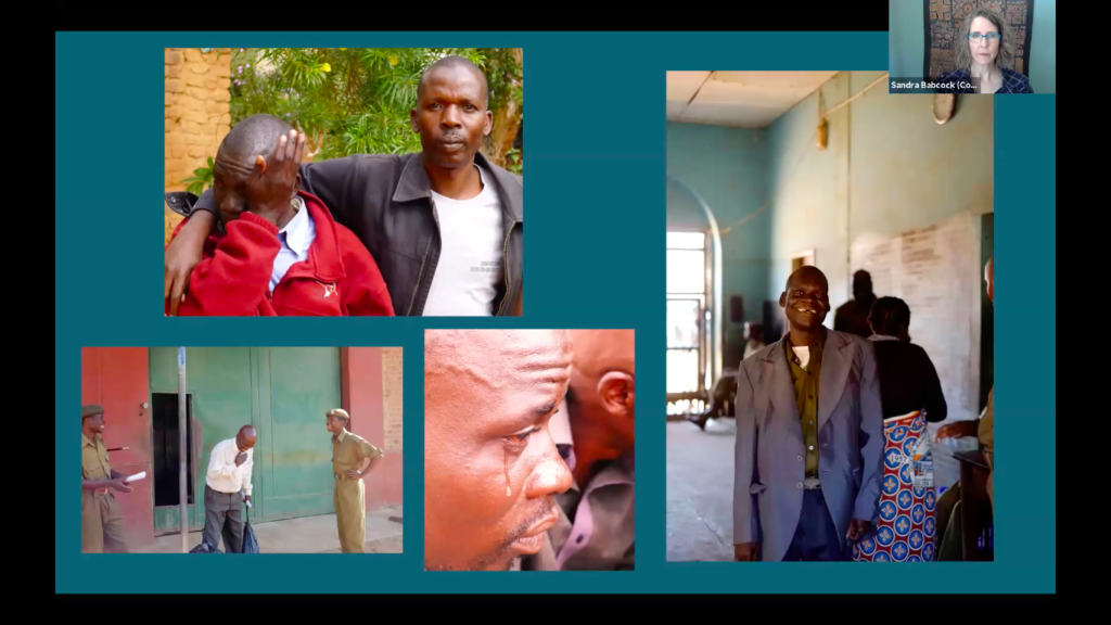 A woman in a video conference, pictured in a small rectangle in the upper righthand corner, looks serious. The rest of the screen shows four photographs. In one photo, a man puts his shoulders around another man, who is wiping his eyes. In another photo, a man holds a hand to his heart as he stand in front of a building between two men dressed in all green. In another photo, a tear falls down a man's cheek. In the final photo, a man wearing a dress shirt smiles at the camera.