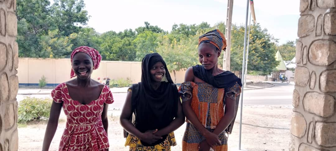 Three women outside smiling and laughing at the camera.