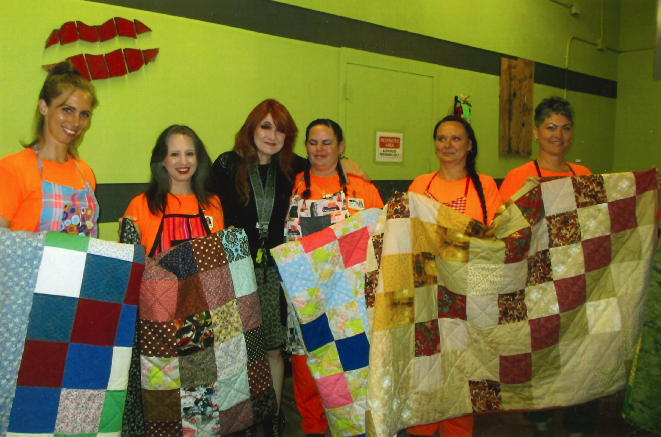 six women holding up quilts.