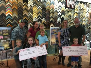 The Marble Family and The Anderson Family displaying their Big Checks in front of the awesome pig bowl collages by Marty Hiser of Westwind Frame and Gallery.  The Actual Checks given to the family were in the amount of $20, 676.42 after more money came in following the initial count.