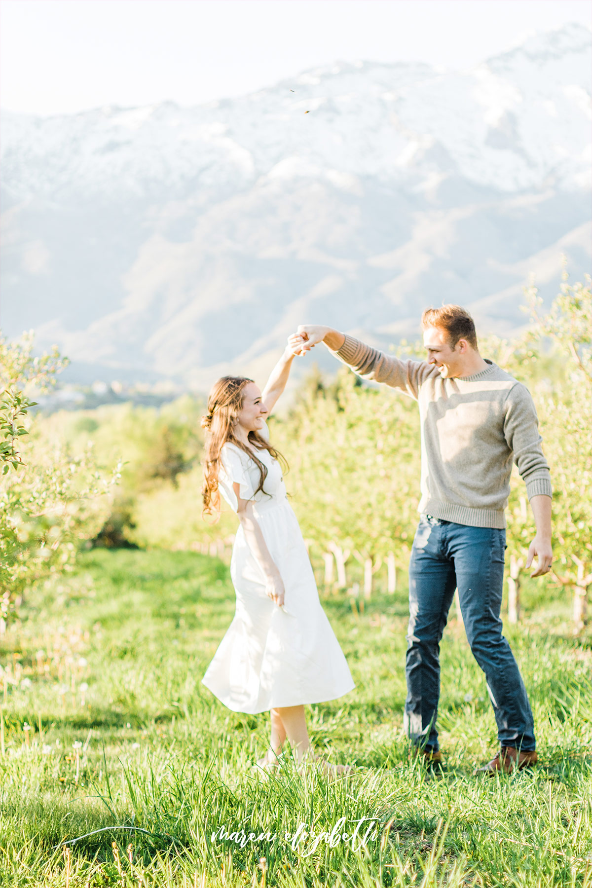 Spring engagement pictures at Burgess Orchards in Alpine, UT with a perfect view of the mountains.   Maren Elizabeth Photography