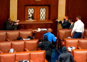 当抗议者试图闯入美国国会大厦的众议院时,警察拿枪防备。 (美联社)