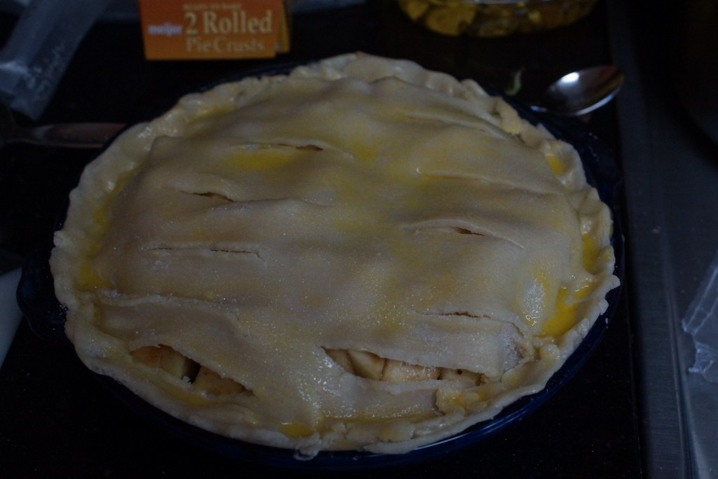 Lay the top crust over the pie, cut slits in the crust, flute the edges, cover with the egg wash and bake.