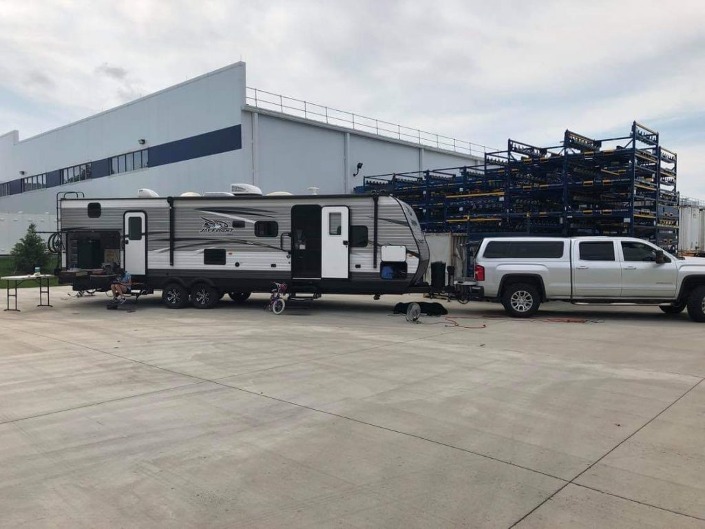Silver GMC Sierra pick up truck with a long Jayco camper attached. They are sitting in a manufacturing facility parking lot.