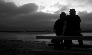 Dark photo of two people on a bench