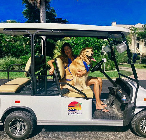 woman and dog in a sanibel cart