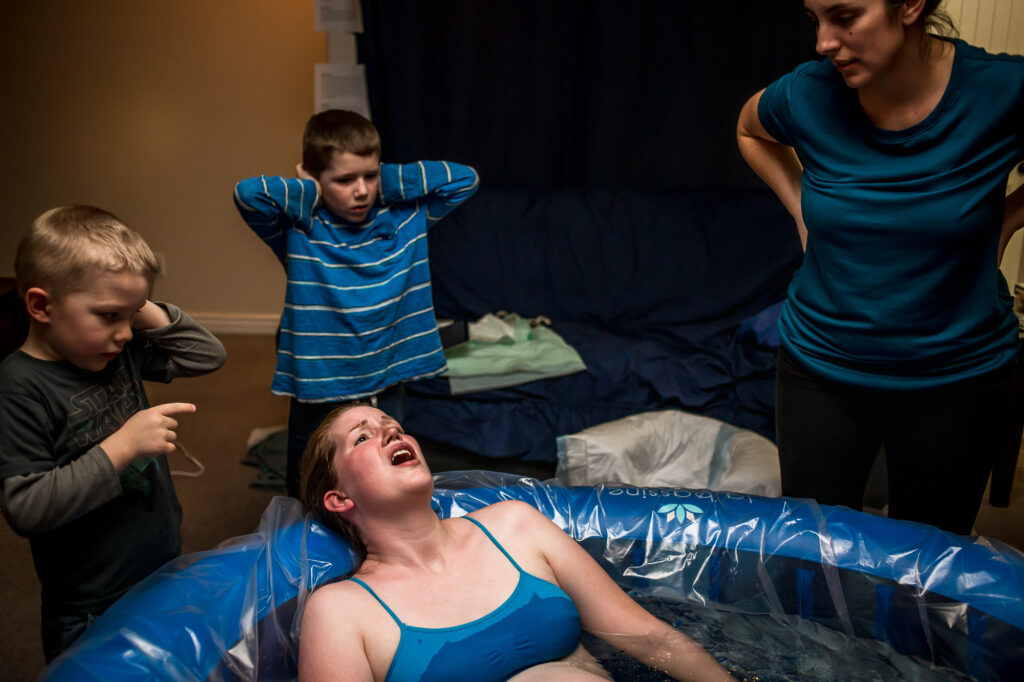 Alisa lets out a roar during a contraction while her children cover their ears. At a home birth in lehi Utah