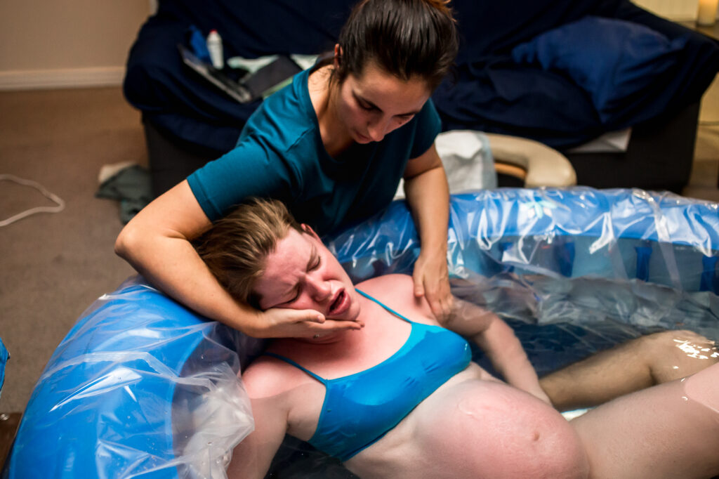 Katie holds Alisa as she pushes at her home birth in lehi Utah