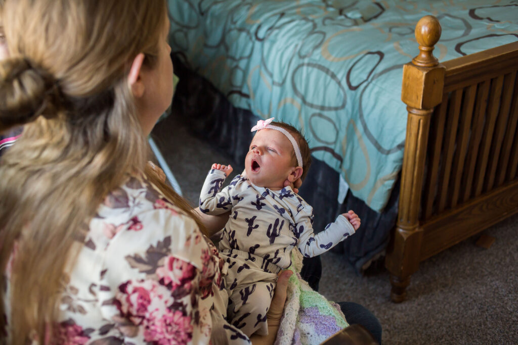 Julia gazes at baby Sarah at a newborn session in Mapleton