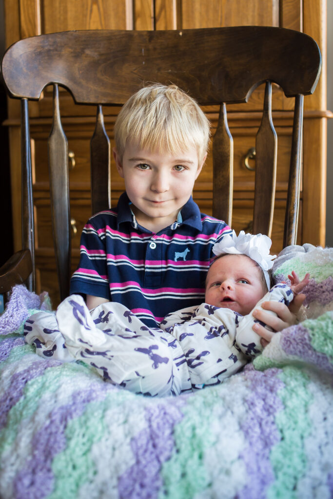 Big brother David smiles as he proudly holds his new baby sister at their newborn session in Mapleton.