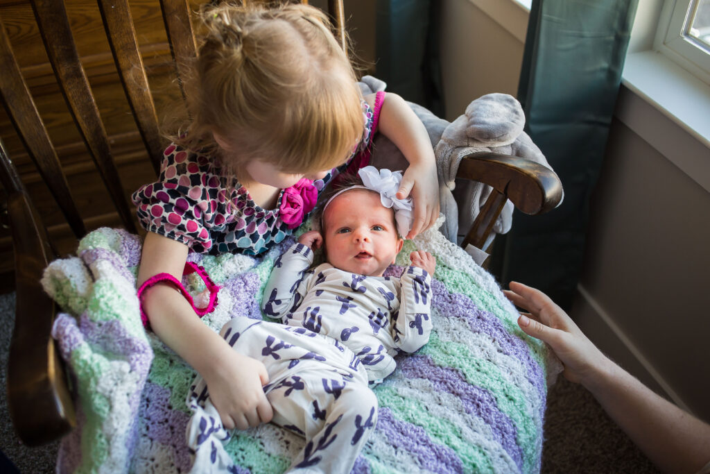 Newly made big sister Charlotte takes her turn holding baby Sarah during pictures during a newborn session in Mapleton