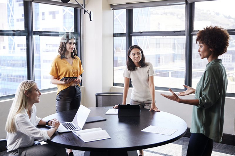 Team Of Young Businesswomen In Meeting Around Table In Modern Workspace