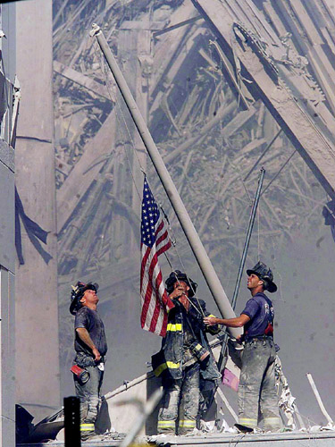 Firefighters raise a flag at the World Trade Center in New York on Tuesday, Sept. 11, 2001, as work at the site continues after hijackers crashed two airliners into the center. (AP Photo/The Record, Thomas E. Franklin)