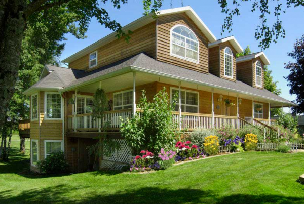 Custom Two-Story modular home with a wrap around covered porch and dormers.