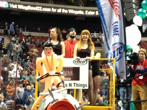 """Dave """"DJ"""" Brunelli enters on the first float of Wing Bowl 22 last Friday. A mock broadcast booth, the rubber doll affixed to a cannon was his entourage's """"goodbye"""" to Chris Wheeler. -photo by Joe Darrah"""