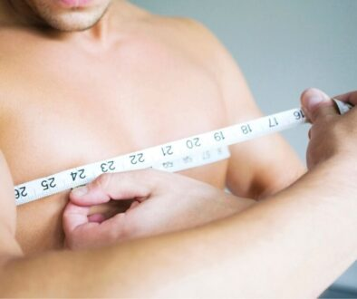 A man with man boobs checking his breast's measurement