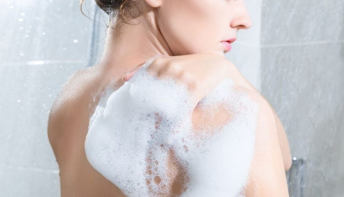 A picture of a woman inside her bathroom using her non toxic body wash