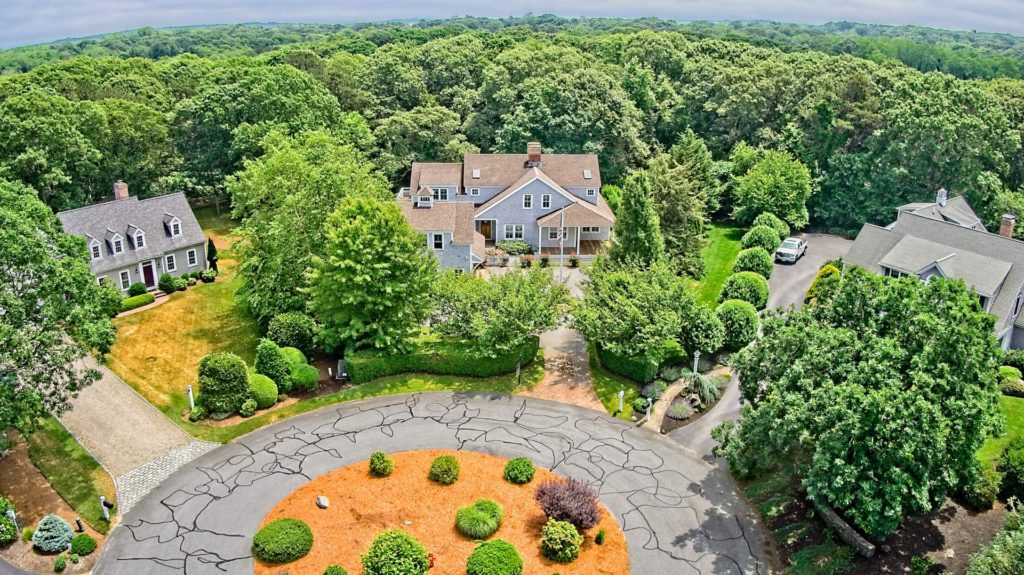 Aerial (drone) view of the front of a luxury 2-story colonial style home in East Sandwich, MA.
