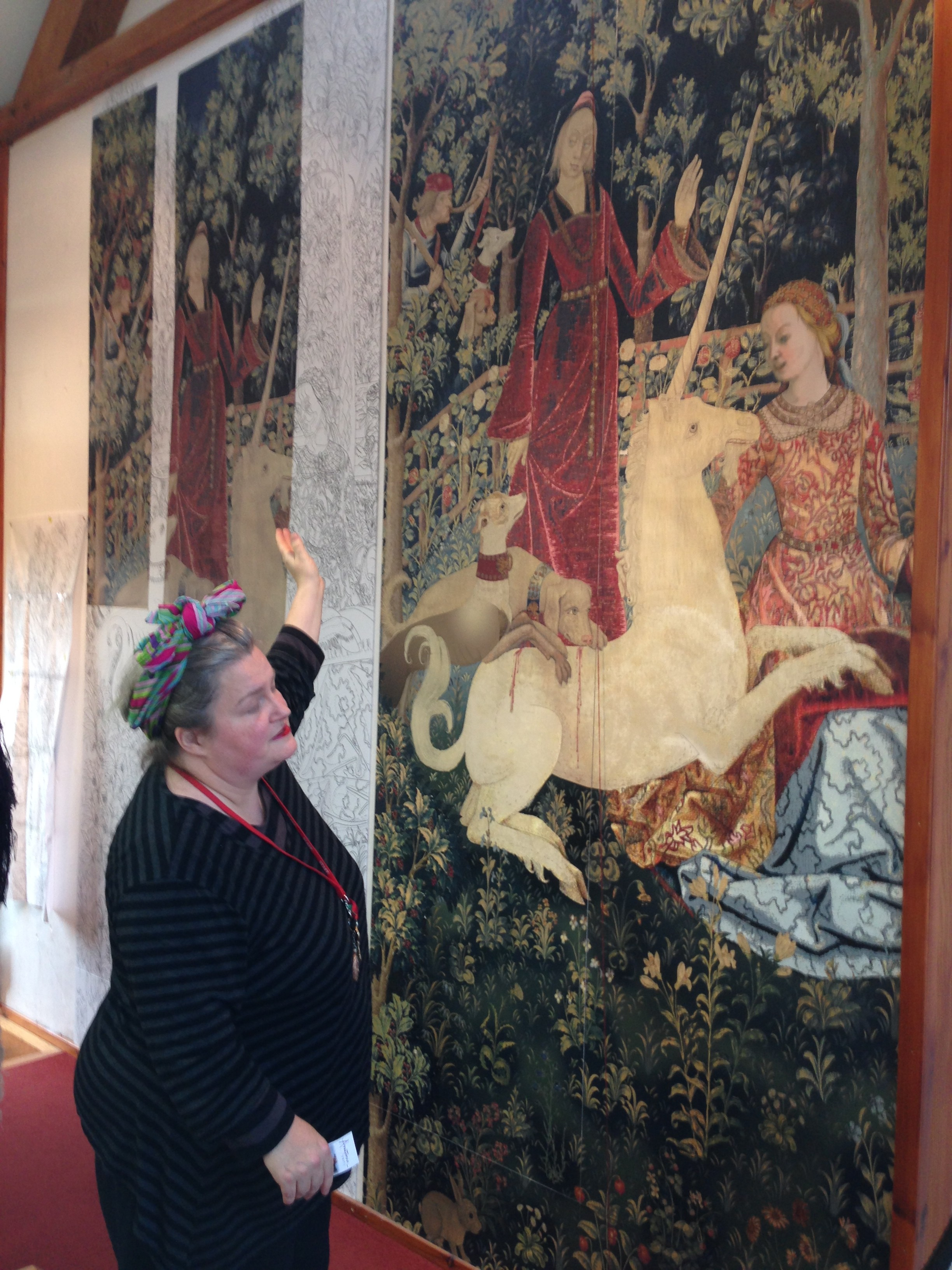The two fragments that exist are hung behind the weaver, together with the drawing of what experts believe the full tapestry might have been.  The weaver is looking at the full drawing, that the weavers are producing as tapestry.