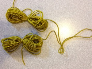 Find the two ends of the strand, and put them together in one hand.  Then pull along the joined strands with the other hand, until you reach the middle.  Tie a slip knot to mark the spot.  Then, wind one end into a yarn butterfly, and then the other.  You will have 2 yarn butterflies joined by the slip knot.  To knit, undo the slip knot and knit from the center of the strand.