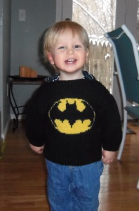"""Owen, modeling the """"Batman"""" sweater that Gramma Mary knit for him.  That is a happy, handsome superhero, if I ever saw one."""