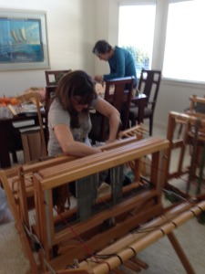 """I'm """"sleying the reed"""", which means pulling the warp threads individually through the fixed slots in the reed.  Jen is behind me, working on the warp for her rigid heddle loom."""