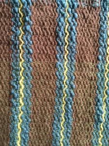 Striped Cotlin warp, except the Blue which is an unknown boucle. Using Reverse twill pattern, which gives a zig zag impression with the stripes. Cool.