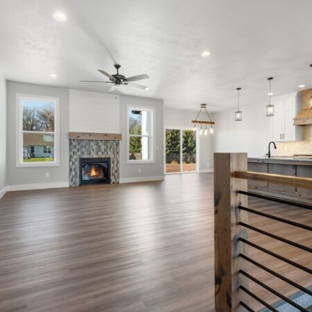 Open living space with gas fireplace and modern stair railing in new home built by Virtue Homes custom home builders.