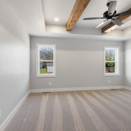 Bedroom with wooden beams and ceiling fan in new home built by Virtue Homes custom home builders.