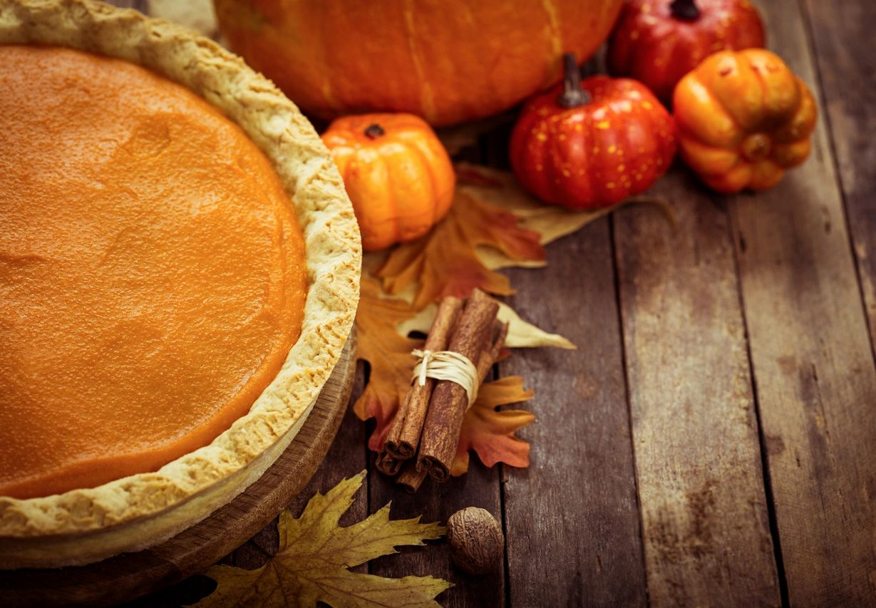 Pumpkin pie display with mini pumpkins and fall leaves