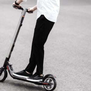 This image is being used as the main image for our article on Electric Scooters. It shows a man riding an electric scooter.