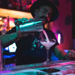 This image shows Marco Balza, head bartender at Tipsy Flamingo, pouring a drink for a guest.